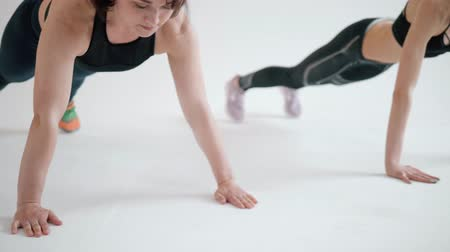 cardio workout : Athletic Beautiful Woman Does Running Plank as Part of Her Fitness, Bodybuilding Gym Training Routine on white background. Stock Footage