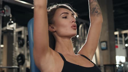 biceps : Brutal young athletic woman pumping up muscules with dumbbells, training girl with barbell in gym indoor Dostupné videozáznamy