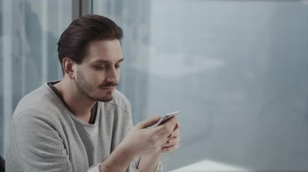 умный : Portrait of young businessman talk on cellphone while stand by his office window in modern interior of skyscraper building, male entrepreneur having mobile phone conversation after important briefing