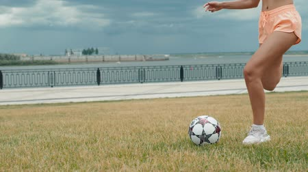 legs only : Young adult girl close up playing football or soccer, kicking a ball with her knee Beautiful brunette woman in a sports suit stand on her legs on a green grass football field against empty stadium city park Stock Footage