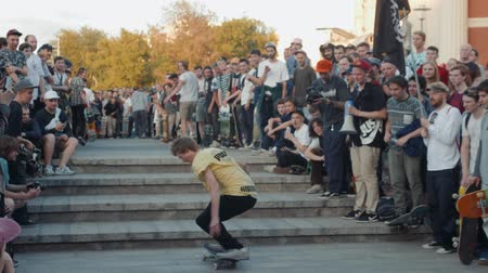 kickflip : 21 JUNE 2018, MOSCOW, RUSSIA, ARBAT, GO SKATEBOARDING DAY: crowd skaters, young professionals and amateur athlete boy is drive on skateboard, eco transportation, making tricks slides and flips city streets, happy students drive on boards and longboards an