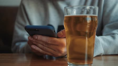 bad habits : people, leisure and technology concept - close up of man with smartphone drinking beer and reading message at bar or pub
