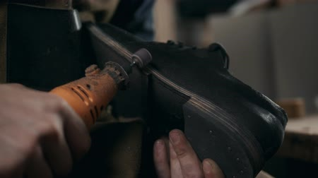 him : shoemaker makes shoes for men He polishes sole of shoe handmade craft production factory leather boots Stock Footage