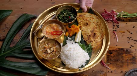 Assorted indian sri-lanka food set on wooden background. Dishes and appetisers of indeed cuisine, rice, lentils, paneer, samosa, spices, masala. Bowls and plates with indian food top view chicken carry Stock Footage