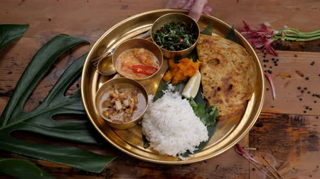 Assorted indian sri-lanka food set on wooden background. Dishes and appetisers of indeed cuisine, rice, lentils, paneer, samosa, spices, masala. Bowls and plates with indian food top view chicken carry Stok Video