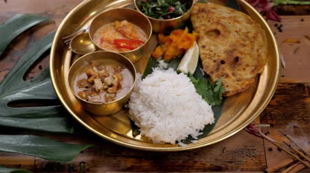 tikka : Assorted indian sri-lanka food set on wooden background. Dishes and appetisers of indeed cuisine, rice, lentils, paneer, samosa, spices, masala. Bowls and plates with indian food top view chicken carry Stock Footage