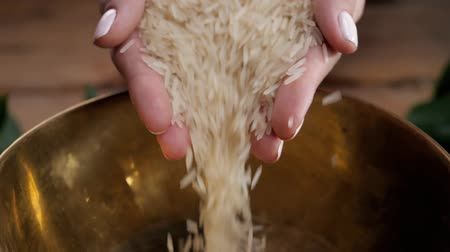 Female hand pouring white brown rice, closeup, close up pour woman in metal bowl before cooking slow motion