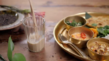 yoghurt : Beautiful and homemade fresh Indian sri lankian drink - mango lassi. On wooden table, garnished with fresh mint. Natural light, with carry traditional food rice