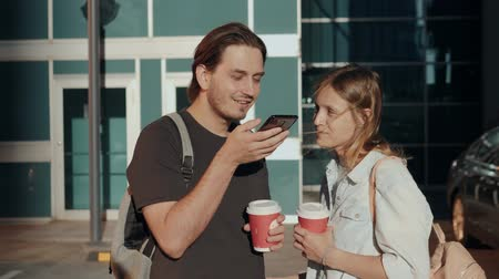 Leisure, technology, communication and people concept - young man and woman using voice command recorder helper or calling on smartphone at street, students voice recognition message with coffee Stock Footage