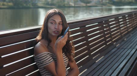 колледж : Happy girl student using a smart phone in a city park sitting on a bench, young woman smiling use application, long brunette hair Стоковые видеозаписи