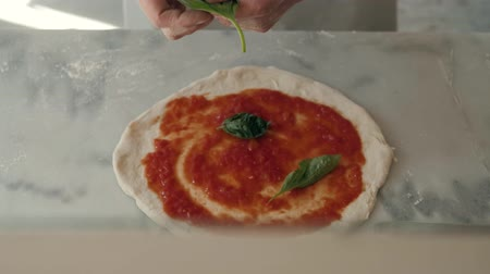 プロシュート : Chef in the restaurant prepares a pizza and decorates it with tomato mozzarella and basil
