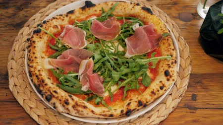 ham : Chef in the pizzeria prepares a pizza and decorates it with prosciutto. Green herbs close up