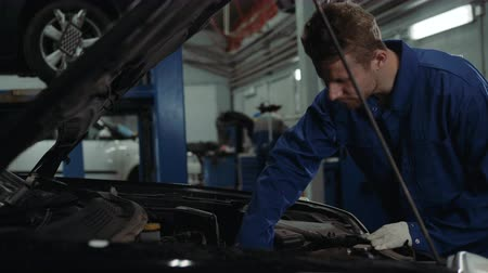 filling station : Mechanic checking oil level in a car workshop man portrait engine car repair service Stock Footage