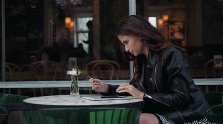 nfc : Young woman holding credit card and using laptop computer. Online shopping concept in modern cafe happy brunette girl student tourist on vacation Stock Footage