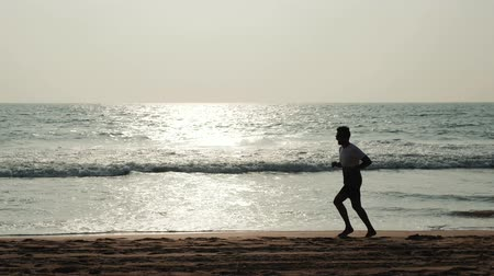 tourist silhouette : silhouette student tourist young athlete runner man with fit strong body training on beautiful Summer sunset beach sand running barefoot in sport well being and healthy lifestyle concept