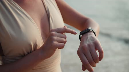 手首 : Active lifestyle woman looking tech smartwatch smart watch. Closeup macro close up arm beach touch screen on wrist band of person relaxing use sport application ai audio message voice recognition