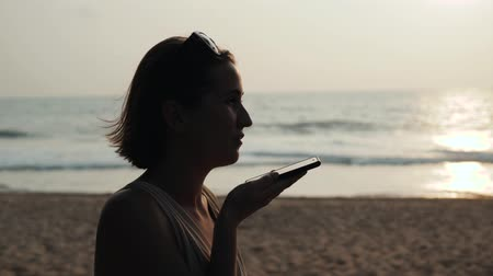 tomar : Silhouette young tourist woman use phone smartphone audio message voice recognition application ai during sunset in ocean beach handsfree. Always connected, the concept of Internet technology. Stock Footage