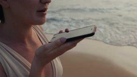 uznání : Girl young tourist woman use phone smartphone audio message voice recognition application ai during sunset in ocean beach handsfree. Always connected, the concept of Internet technology on vacation travel.