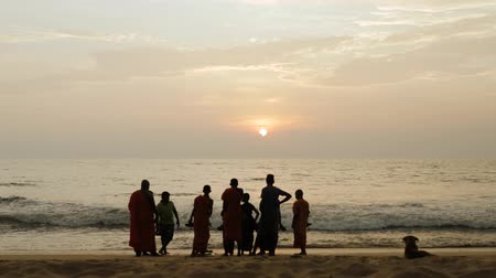 alms : BENTOTA 09 FEBRUARY 2019 SRI LANKA: silhouettes of buddhist monks standing on the ocean and watching the sunset
