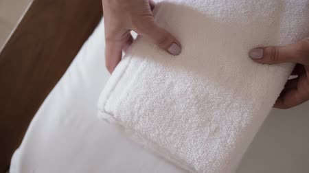 towel folded : Close-up of hands putting stack of fresh white bath towels on the bed sheet. Room service maid cleaning hotel room macro closeup Stock Footage