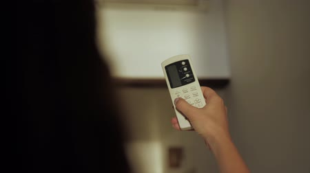 enable : Air conditioner inside the room with woman operating remote controller.  Air conditioner with remote controller hotel room