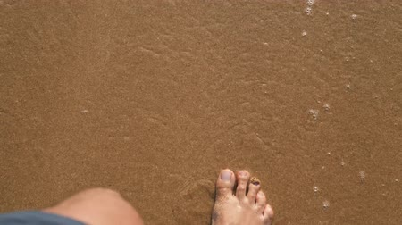 mezítláb : Beach travel man walking wave ocean sand beach leaving footprints in the sand. Closeup detail of male feet close up macro pov top view Stock mozgókép