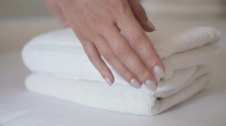 dobrado : Close-up of hands putting stack of fresh white bath towels on the bed sheet. Room service maid cleaning hotel room macro closeup Vídeos