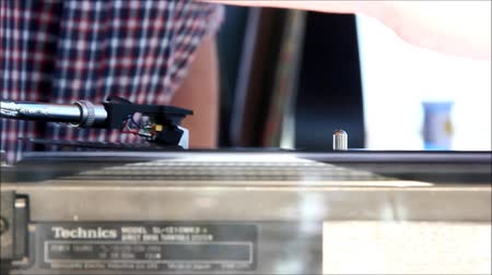 rpm : Close Up of a Turntable Arm with a Vinyl Record Bending with the Warmth of the Sun