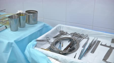 internar : Medical equipment. Surgical instruments and tools including scalpels, forceps and tweezers arranged on a table for a surgery