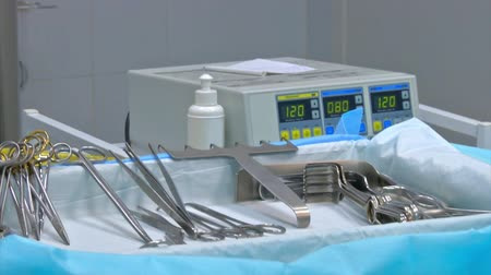 ér : surgical instruments and tools including scalpels, forceps and tweezers arranged on a table for a surgery