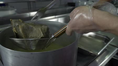 coletando : Dumplings are cooked in a saucepan of boiling water. Pull hot dumplings out of the pan using a ladle.