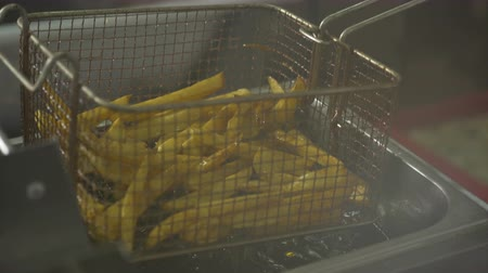 crocante : 4K In the kitchen fried french fries in hot oil in slow motion. Vídeos
