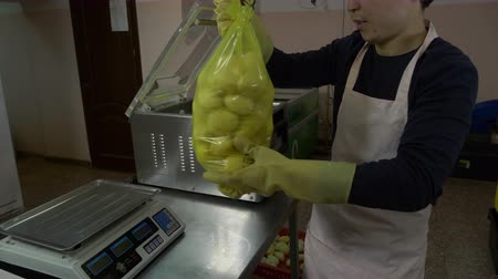 raiz : A man puts a packet of potatoes in a vacuum packer.