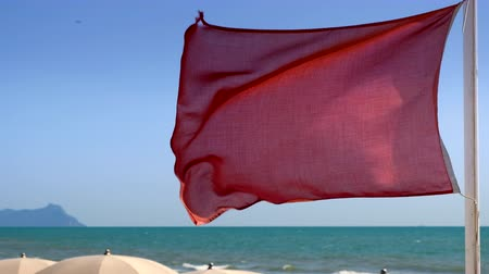 cloud scape : Red flag blowing in the wind on the beach. No people.
