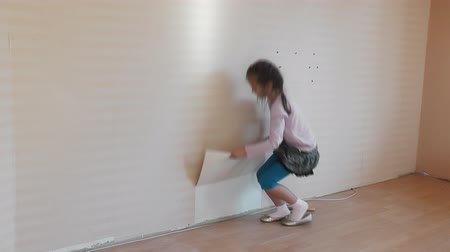 wall paper : Girl removing a wallpaper in  house.