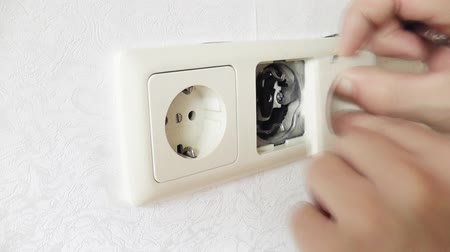 elektryk : Man installs an electrical socket