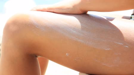 молодые женщины : Woman on beach applying sun block lotion on her legs