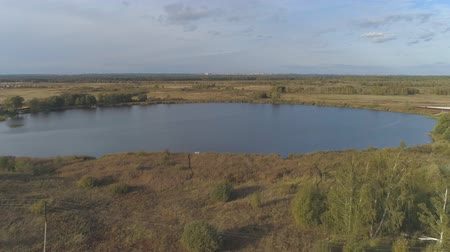 Fly away from the lake Yakushinsky. Aerial video shooting in nature in the Vladimir region.