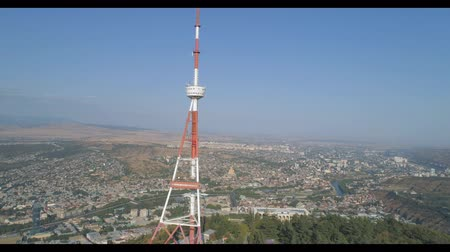 High TV tower in the park Mtatsminda on the mountain. Aerial video shooting in Georgia. Dostupné videozáznamy