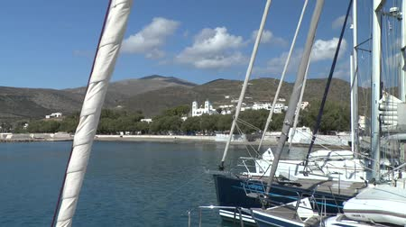 такелаж : View of a Greek seaside town through the rigging of yachts moored in the marina, Amorgos island, Greece.