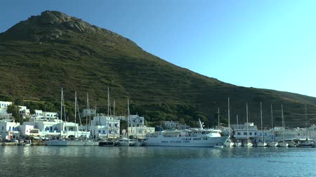 жилье : Vessels in the harbor of the coastal town at the base of the mountain. Amorgos, Greece. Стоковые видеозаписи