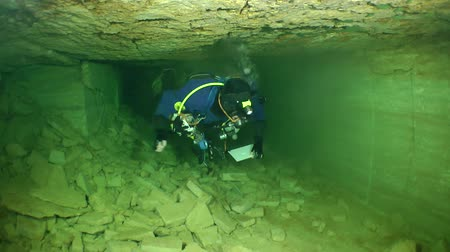 subterranean : Speleologist swims up to the bifurcation of the corridor of flooded mine.