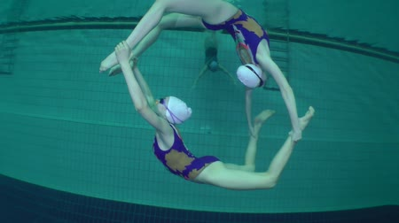 soutěže : Synchronized swimming, two girls form a ring, and the third girl swims through it, underwater.