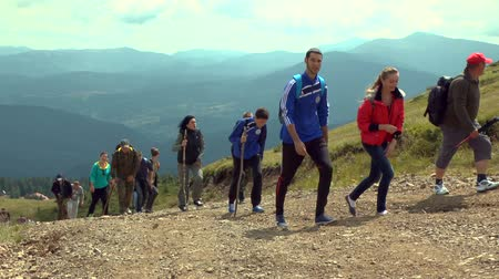A group of tourists climbs the mountain road against the backdrop of distant mountains. Dostupné videozáznamy