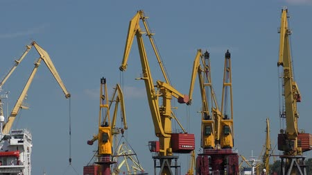 партия : Loading the ship in the port, the cranes work.