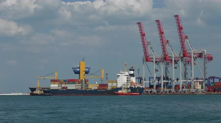 atracação : A large container ship leaves the port.