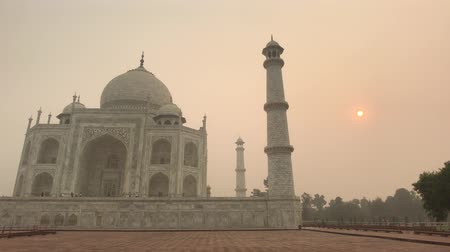 geliştirmek : Agra, India, November 10, 2019, Taj Mahal, mosque with tower at sunrise 4K
