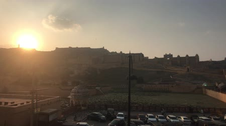geliştirmek : Jaipur, India, November 05, 2019, Amer Fort, tourists walk in the parking lot against the sunrise 4K