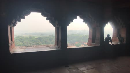 astroloji : Agra, India, November 10, 2019, Agra Fort, tourists talk sitting on the window 4K Stok Video