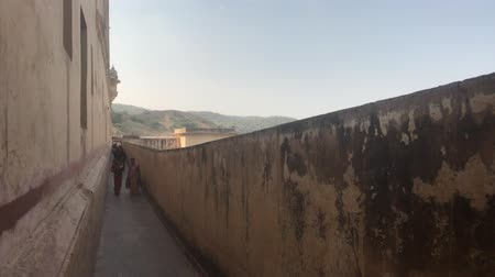 slum : Jaipur, India, November 05, 2019, Amer Fort tourists walk along the long balcony of the fortress 4K